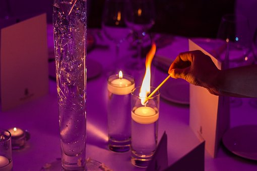 table de fête, avec une main qui allume une bougie