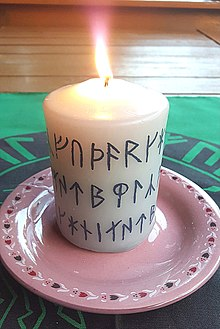 lighted white candle with printed runes