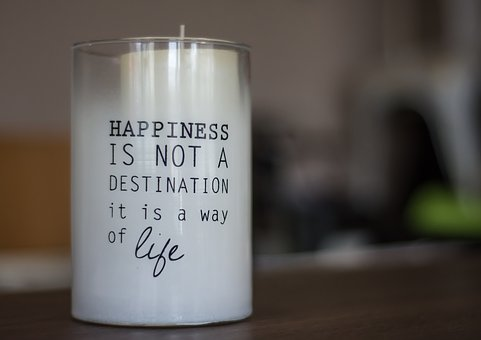 """white candle in pot on which it is marked """"happiness is not destination it's life"""""""