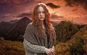 Femme rousse en chandail gris devant un paysage de montagne