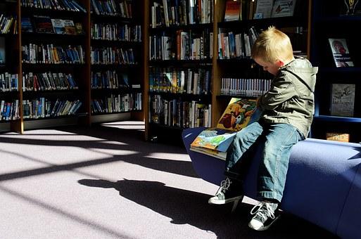 un enfant assis qui lit un livre de contes et légendes