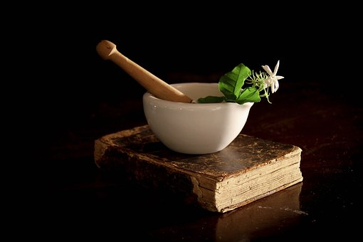 mortar and pestle on a magic recipe book