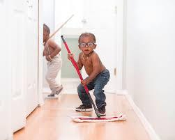 petit garçon afro qui passe la serpillière pour aider ses parents.