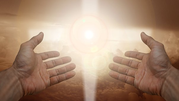 two hands stretched with bright light between the two