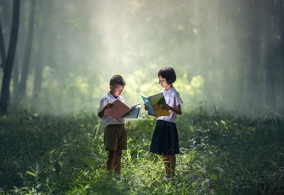 deux enfants qui lisent un livre face a face dans une foret